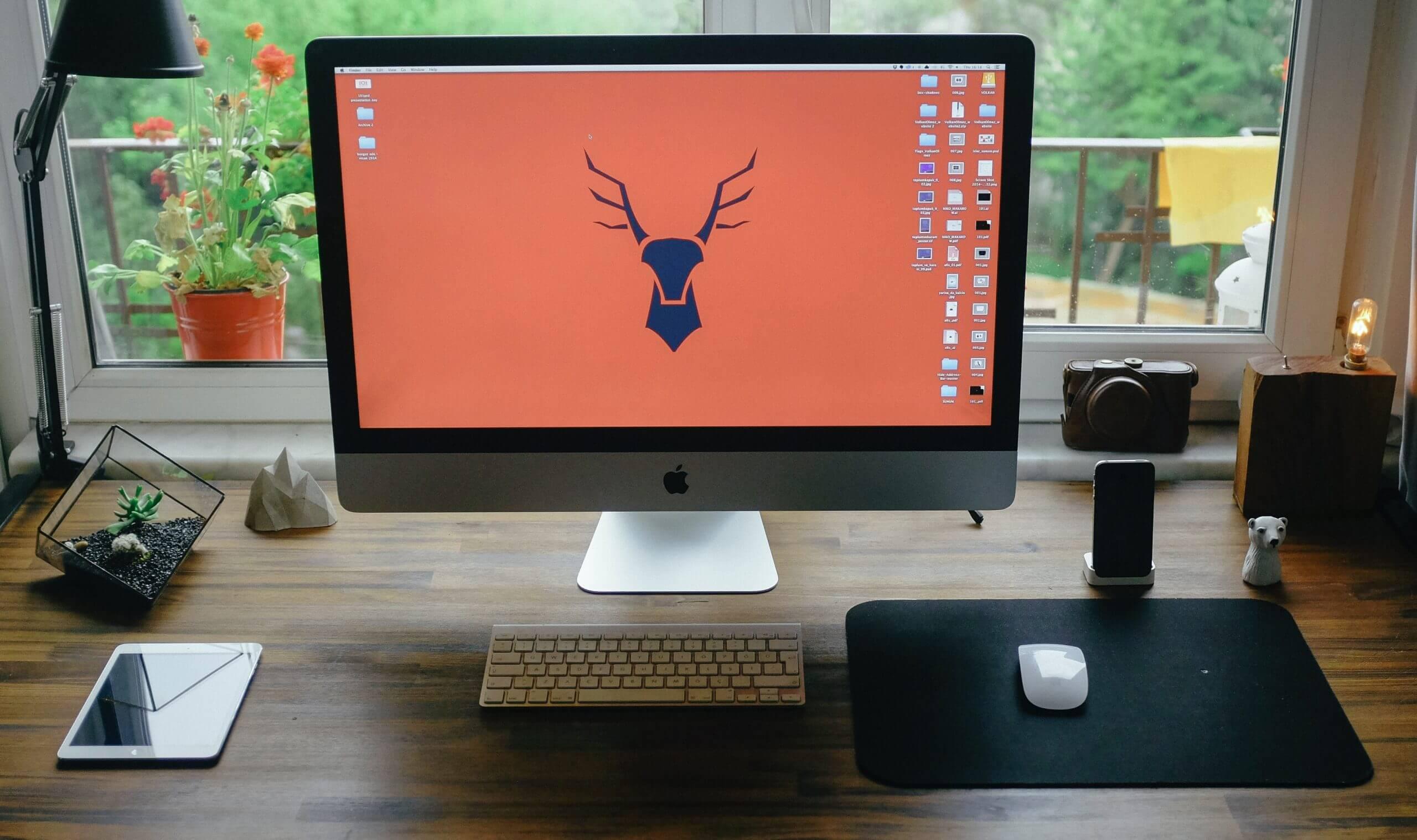 Logo tête de cerf sur l'écran d'un ordinateur posé sur un bureau