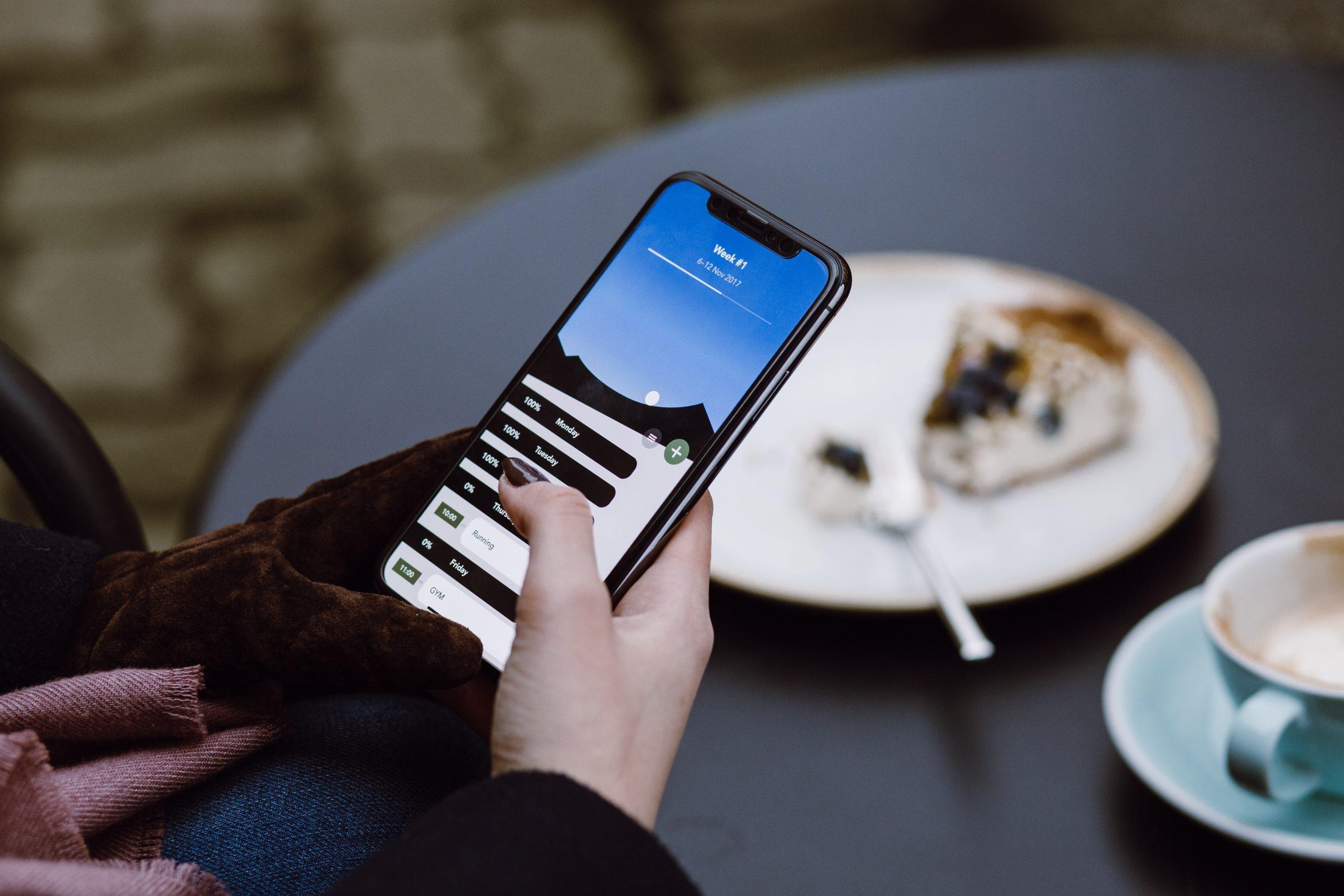 Homme qui mange un dessert et fait une recherche sur un smartphone