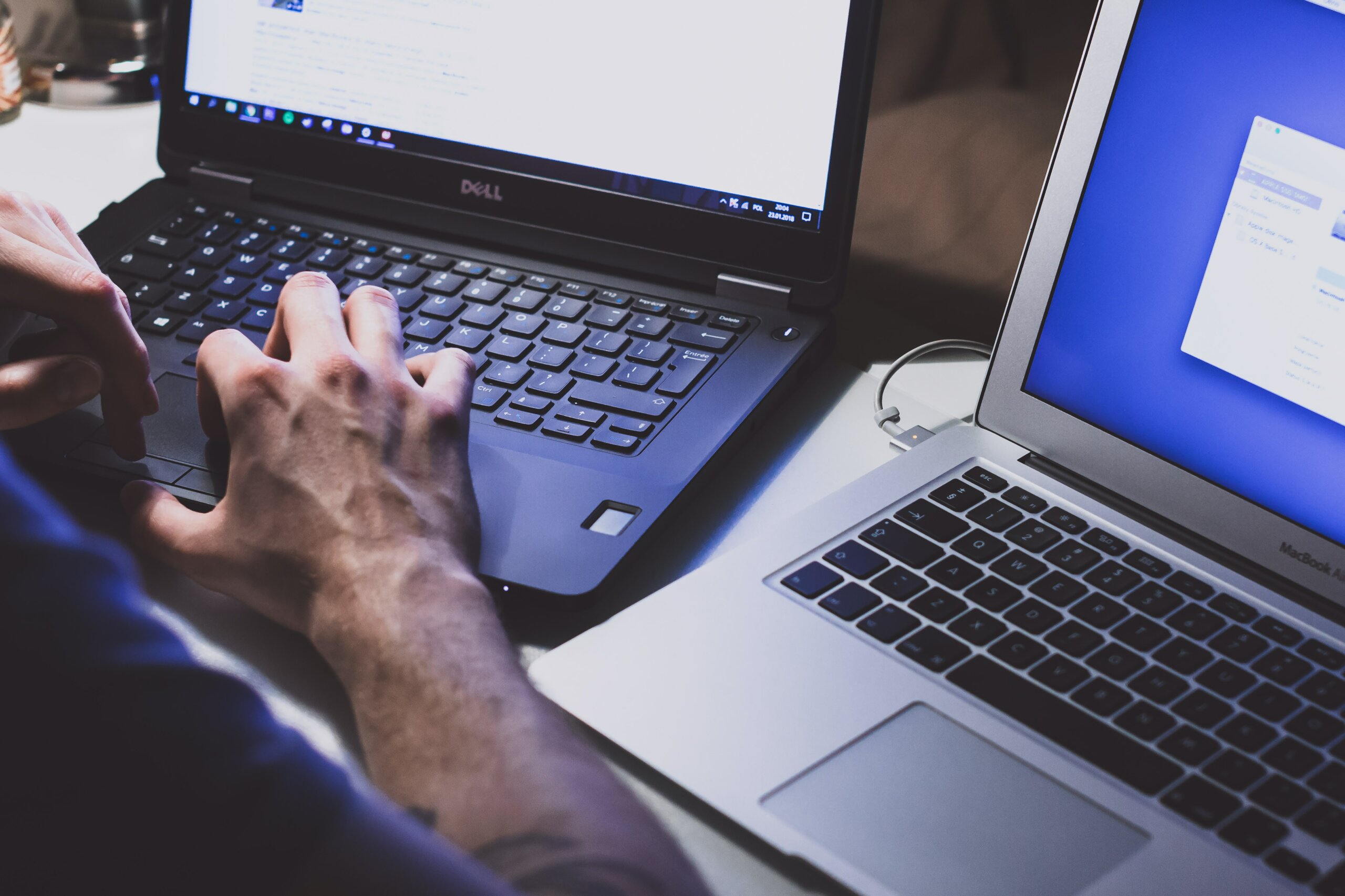 Informaticien travaillant sur deux ordinateurs portables